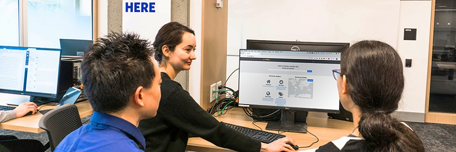 Three students sit at a computer with Geodisy on the screen. One student is showing the other two how to use the software and is smiling. The two other students have their  back to the camera.